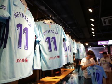 People stand next to t-shirts with the name of FC Barcelona's Neymar in a store of the Camp Nou stadium in Barcelona, Spain, Wednesday, Aug. 2, 2017. Neymar has told Barcelona that he plans to leave the club, with a blockbuster move to Paris Saint-Germain seemingly imminent. (AP Photo/Manu Fernandez)