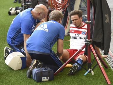In this Aug. 19, 2017 photo Hamburg's Nicolai Mueller is treated during the German Bundesliga soccer match between Hamburger SV and FC Augsburg in Hamburg, Germany. Hamburger SV forward Nicolai Mueller is out for around six months after injuring himself while celebrating a goal. The Bundesliga club says Mueller tore a cruciate ligament in his right knee after scoring in Saturday's league-opener, a 1-0 home win over Augsburg. Mueller attempted a pirouette before falling to the ground in apparent pain. (Daniel Bockwoldt/dpa via AP)