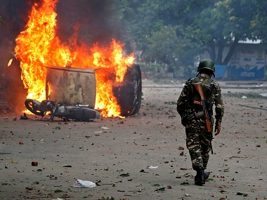 A member of the security forces walks towards a burning vehicles  during violence in Panchkula,. Reuters