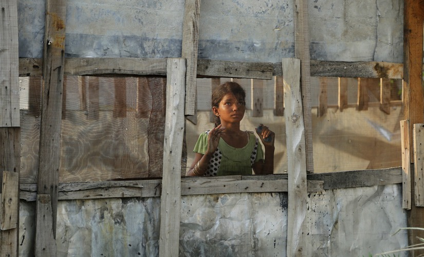 A Rohingya refugee girl looks through a mesh window at a camp set up for the refugees on the outskirts of Jammu, India. AP