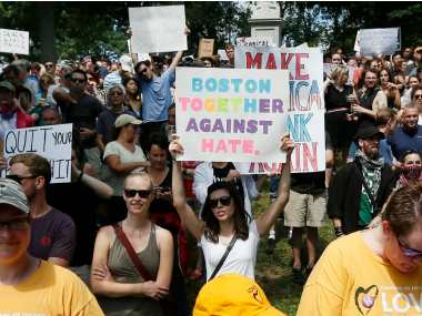 "Counterprotesters hold signs at a ""Free Speech"" rally by conservative activists on Boston Common, Saturday. AP"