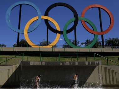 Children play in water near Olympic rings placed at Madureira Park for the Rio 2016. Reuters