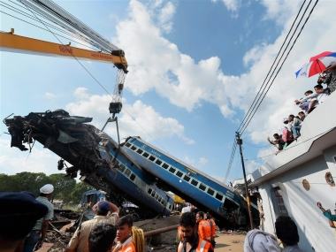 A mangled coach of the Utkal Express being hauled off the tracks. PTI