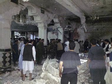 Civilians and security forces inside the mosque after the suicide attack. AP