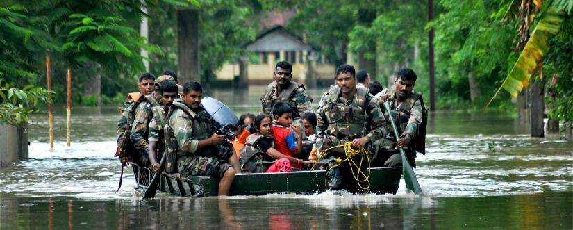 NDRF personnel rescue people affected by flash floods in Assam on Monday. PTI
