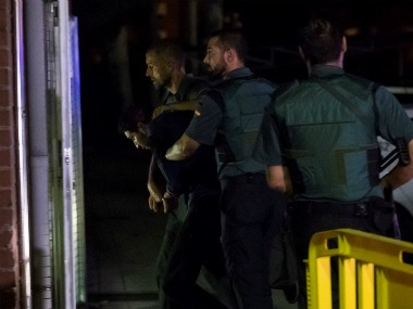 Spanish civil guards escort one of four men accused of involvement in an Islamist cell behind a van attack in Barcelona. Reuters