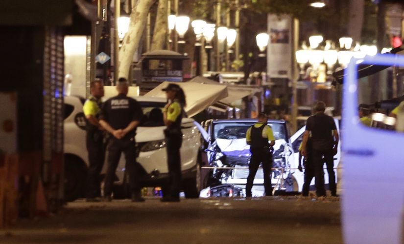 Police officers stand next to the van involved in Thursday's attack in La Rablas in Spain's Barcelona. AP