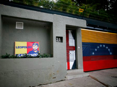 A banner with the image of opposition leader Leopoldo Lopez stands outside of his home in Caracas, Venezuela, Tuesday, Aug. 1, 2017. Allies of two Venezuelan opposition leaders say Lopez and Antonio Ledezma have been taken by authorities from the homes where they were under house arrest. Video posted on the Twitter account of Lopez's wife early Tuesday, Aug. 1, shows a man being taken away from a Caracas home by state security agents. AP