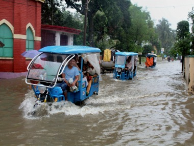 Vehicles ply through a waterlogged road after heavy rains at Balurghat in South Dinajpur district of West Bengal on Sunday. PTI