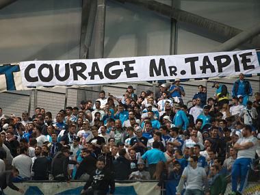 """Om's fans cheer next to a banner reading """"Be brave M. Tapie"""" in tribute to OM's former president hospitalized in Paris, prior to the French L1 football match Olympique de Marseille vs Toulouse on September 24, 2017 at the Velodrome stadium in Marseille, southern France. / AFP PHOTO / BERTRAND LANGLOIS"""