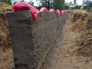 The wall that the Odisha government is building around a 1,700 hectare piece of land on Nuagaon village's periphery to mark the inclusion of the land in the state government's land bank