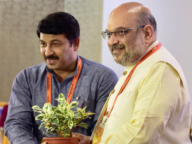 Amit Shah being greeted by Delhi BJP chief Manoj Tiwari during the party office bearers' meeting at NDMC Convention Centre, in New Delhi on Sunday. PTI