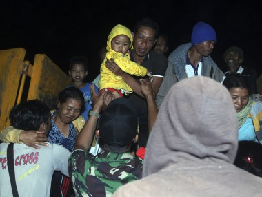 Rescuers assist villagers who were evacuated from their homes on the slope of Mount Agung. AP