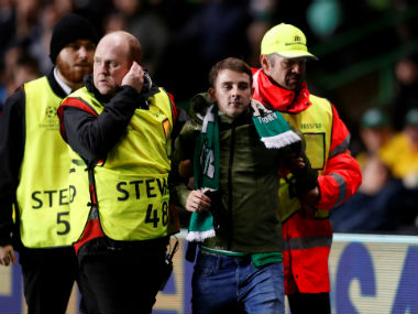 Celtic fan is removed by stewards after invading the pitch. Reuters