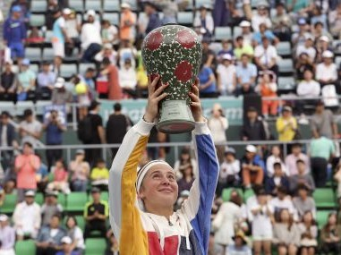 Jelena Ostapenko holds up her winning trophy after defeating Beatriz Haddad Maia. AP
