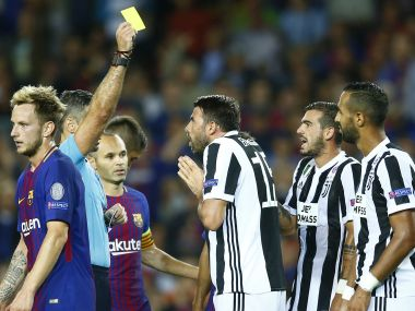 Referee Damir Skomina shows a yellow card to Juventus' Andrea Barzagli during a group D Champions League soccer match between FC Barcelona and Juventus at the Camp Nou stadium in Barcelona, Spain, Tuesday, Sept. 12, 2017. (AP Photo/Manu Fernandez)