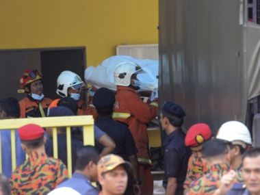 Police and firemen at the scene of the fire in Kuala Lumpur. AP