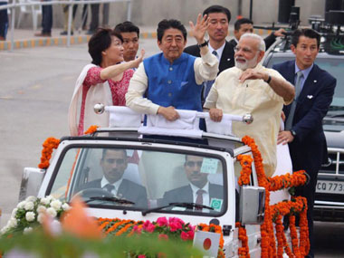 Prime Minister Narendra Modi, Japanese Prime Minister Shinzo Abe and his wife Akie Abe wave from an open vehicle during their roadshow in Ahmedabad on Wednesday. Abe is on a two-day visit to India. PTI