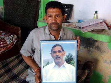 Ram Kishan with a portrait of his father Sundu Ram, who lost his life in the Dera 13 years ago. Sat Singh