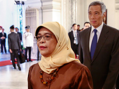 Halimah Yacob walks before taking the oath of office and is followed by Singapore Prime Minister Lee Hsien Loong. AP