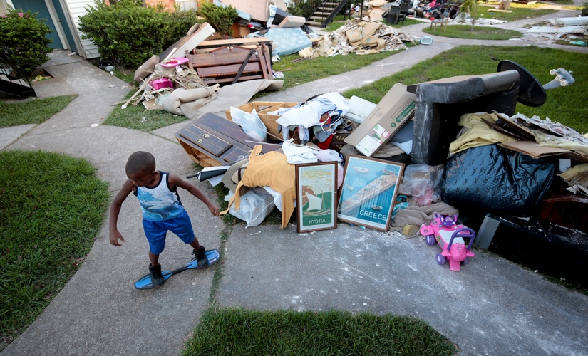 A child next to property damaged due to Hurricace Harvey. Reuters