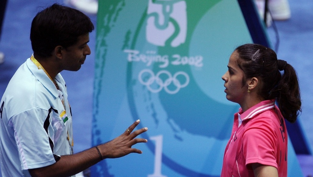 Saina Nehwal (R) listens to coach Pullela Gopichand (L) at the mid-game interval during her women's singes first round match against Russia's Ella Karachkova at the 2008 Beijing Olympic Games — AFP