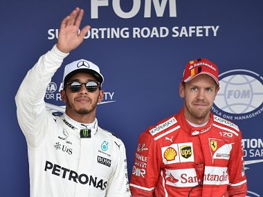 Mercedes' Lewis Hamilton celebrates his pole position alongside Ferrari's driver Sebastian Vettel, who finished 3rd but a penalty to will mean he will start in 2nd place. AFP