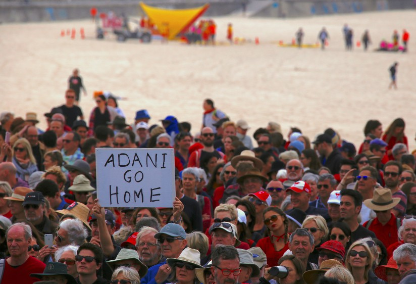 Surf lifesavers are seen behind protesters participating in a national Day of Action against Adani's mining company. Reuters