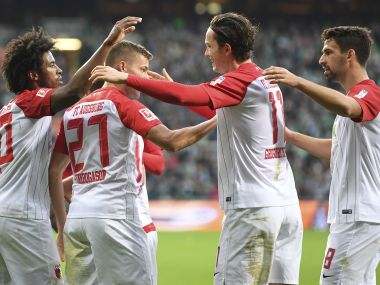 Augsburg's Caiuby, left, Alfred Finnbogason, second left, and Rani Khedira, right, celebrate the opening goal by Michael Gregoritsch, during the match with FC Augsburg. AP