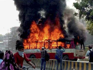 File image of angry supporters setting ablaze a bus during a protest against the murder of BSP leader Rajesh Yadav, in Allahabad on Tuesday. PTI