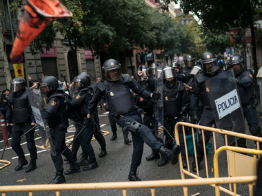 Spanish riot police removes fences thrown by people to them as they try to prevent people from reaching a voting site at a school assigned to be a polling station by the Catalan government in Barcelona on Sunday. AP