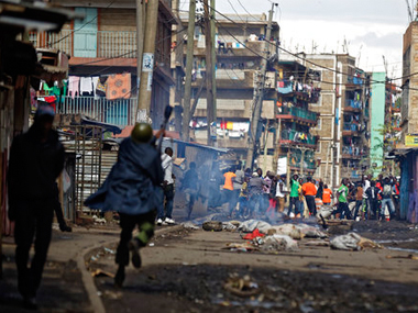 Kenyan riot police charge towards opposition protesters during clashes in the Mathare slum of Nairobi, Kenya. AP