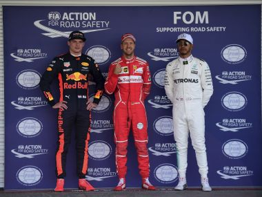 Max Verstappen, left, Sebastian Vettel, center, and Lewis Hamilton, right, pose on the stand after qualifying. AP