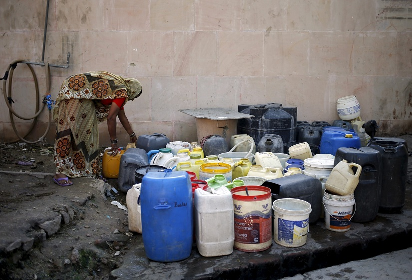 A woman arranges her empty containers as she waits to fill water from a municipal tap in New Delhi, India, February 21, 2016. India deployed thousands of troops in a northern state on Sunday to quell protests that have severely hit water supplies to Delhi, a city of more than 20 million people, forced factories to close and killed 10 people. Rioting and looting in Haryana by the Jats, a rural caste, is symptomatic of increasingly fierce competition for government jobs and educational openings in India, whose growing population is set to overtake China's within a decade. REUTERS/Anindito Mukherjee - GF10000317306