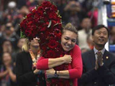 Simona Halep of Romania hugs a floral bouquet in the shape of the number one after beating Jelena Ostapenko of Latvia in their women's singles semifinal in the China Open tennis tournament at the Diamond Court in Beijing, Saturday, Oct. 7, 2017. Halep achieved the women's world #1 ranking with the victory. (AP Photo/Mark Schiefelbein)