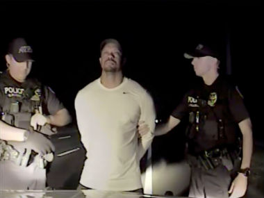 Tiger Woods is seen handcuffed and searched by police officers in this still image from police dashcam video in Jupiter, Florida. Reuters
