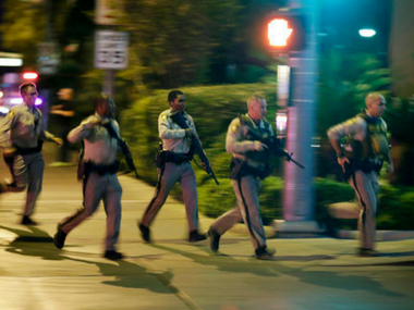 Police run to cover at the scene of the shooting in Las Vegas. AP