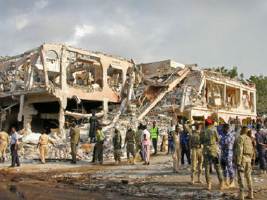 Somali security forces and others gather and search for bodies near destroyed buildings at the blast site. AP