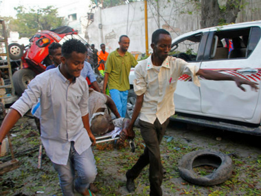 Somalis carry a wounded civilian who was injured in the car bomb on Saturday. AP