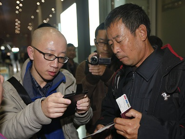 File photo of Chinese dissident Hu Jia (L) at Beijing airport. Reuters