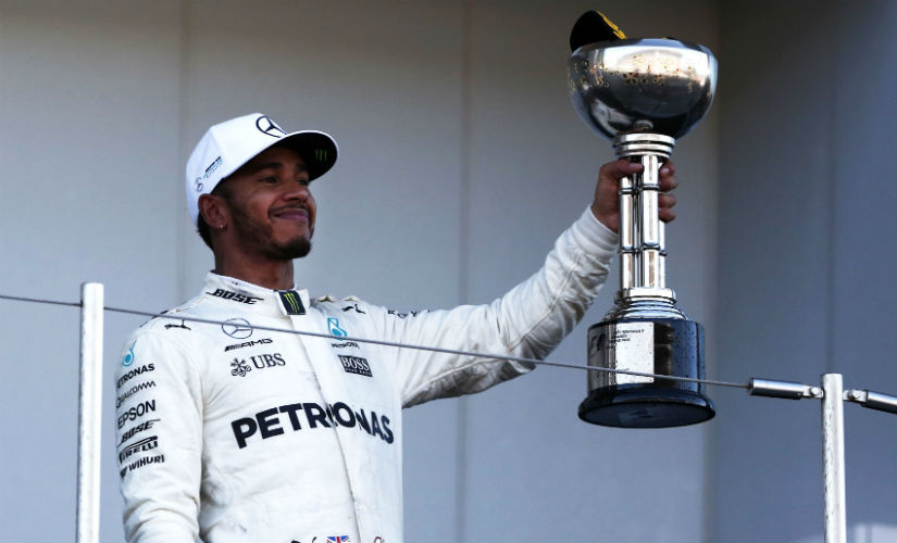 Lewis Hamilton gestures with his trophy at the podium following his win at the Japanese Grand Prix. AFP
