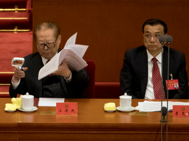 Former Chinese President Jiang Zemin, left uses a magnifying glass to look at documents near Chinese Premier Li Keqiang on Wednesday. AP