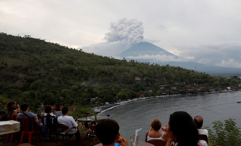 People watch Mount Agung volcano erupt from a cafe near Amed, Bali. Reuters