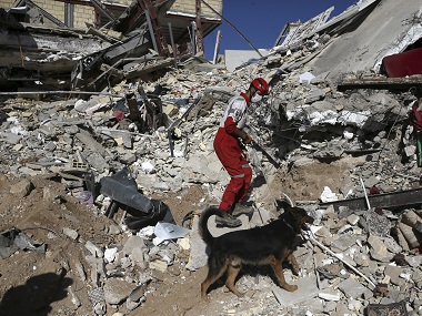 A rescue worker searches the debris with his sniffing dog on the earthquake site. AP