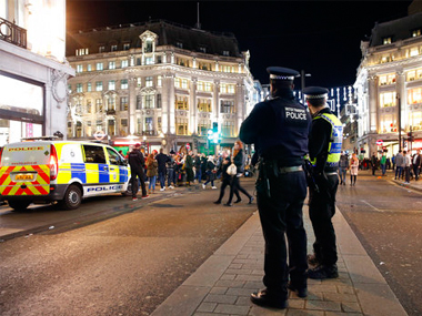 Police officers and vehicles near Oxford Circus subway station in the west of London after it was reopened on Friday. AP
