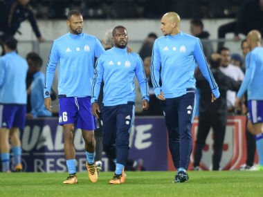 Marseille's French defender Patrice Evra is escorted off the pitch by teammates Portuguese defender Rolando and Brazilian defender Doria after an argument with supporters. AFP