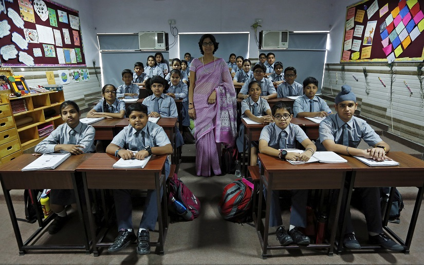 """Teacher Archana Shori poses for a picture with 7th-grade level students inside their classroom at Rukmini Devi Public school in New Delhi, India, September 7, 2015. Nearly three years after Taliban gunmen shot Pakistani schoolgirl Malala Yousafzai, the teenage activist last week urged world leaders gathered in New York to help millions more children go to school. World Teachers' Day falls on 5 October, a Unesco initiative highlighting the work of educators struggling to teach children amid intimidation in Pakistan, conflict in Syria or poverty in Vietnam. Even so, there have been some improvements: the number of children not attending primary school has plummeted to an estimated 57 million worldwide in 2015, the U.N. says, down from 100 million 15 years ago. Reuters photographers have documented learning around the world, from well-resourced schools to pupils crammed into corridors in the Philippines, on boats in Brazil or in crowded classrooms in Burundi. REUTERS/Adnan AbidiPICTURE 3 OF 47 FOR WIDER IMAGE STORY """"SCHOOLS AROUND THE WORLD""""SEARCH """"EDUCATORS SCHOOLS"""" FOR ALL IMAGES - RTS2DU2"""