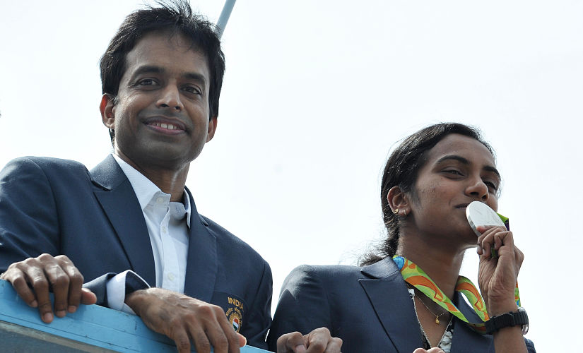 Indian badminton player and Olympic silver medalist P.V Sindhu (R) and her coach P. Gopichand take part in a parade after arriving home from the Rio Olympics in Hyderabad on August 22, 2016. India swelled with pride August 20 after badminton champion P.V. Sindhu became the first woman in the country's history to win an Olympic silver medal. / AFP PHOTO / NOAH SEELAM