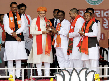 Prime Minister Narendra Modi being presented a memento by the supporters during an election campaign rally, at Dhandhuka village of Ahmedabad district on Wednesday. PTI