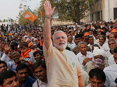 BJP supporters carry a cut out of prime minister Narendra Modi after an election campaign rally at Surendranaga, Gujarat. AP
